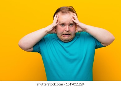 young big size man screaming with hands up in the air, feeling furious, frustrated, stressed and upset against orange wall