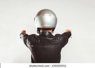 Young biker from back in a Leather jacket pretending to ride a motorcycle isolated on white background
