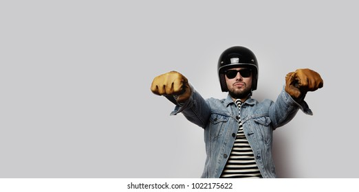 Young biker in a blue denim jacket pretending to ride a motorcycle isolated on white background. Horizontal. Wide
