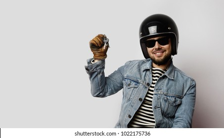 Young biker in a blue denim jacket pretending to ride a motorcycle isolated on white background.Man holding hand moto keys. Horizontal