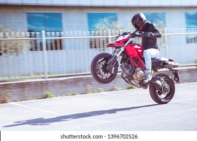 young biker doing a wheelie on his motorcycle.