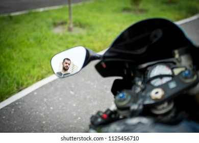 A young biker in the mirror reflection on a motorcycle. Reflection of a biker in the mirror of a motorcycle. A young guy stands next to a sports motorcycle and is reflected in a mirror.