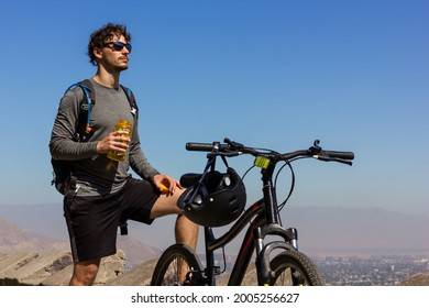 Young biker with sunglasses holding water bottle next to mountain bike on sunny day. Handsome man taking a break while and enjoying splendid views of Santiago city in Chile