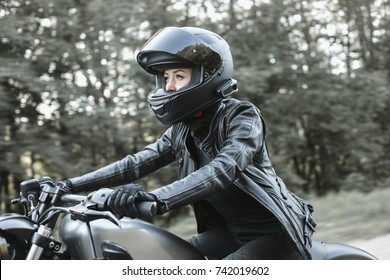 Young biker woman riding chopper motorbike on forest road