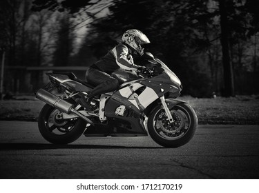 Young biker woman riding sport motorbike on road. Black and white