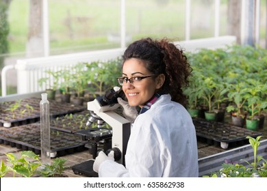 Young biologist sitting at microscope with seedlings around her in greenhouse and looking in camera over her shoulder. Microbiology, biotechnology and bioengineering concept