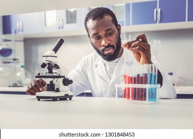 Young biotechnologist. Bearded young biotechnologist feeling concerned while working with innovative glass tubes