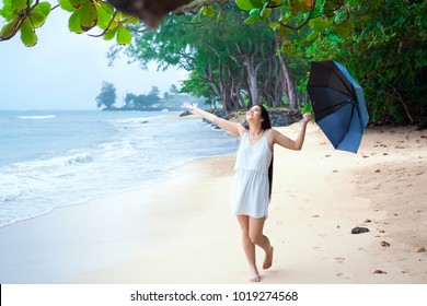 Young biracial Asian Caucasian woman or teen walking on beach holding umbrella on overcast rainy day, arms outstreched enjoying the rain, smiling