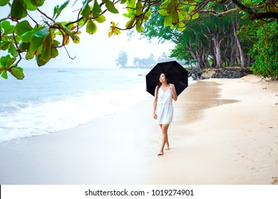 Young biracial Asian Caucasian woman or teen walking on beach holding umbrella on overcast rainy day, looking out over the water with sad or lonely expression