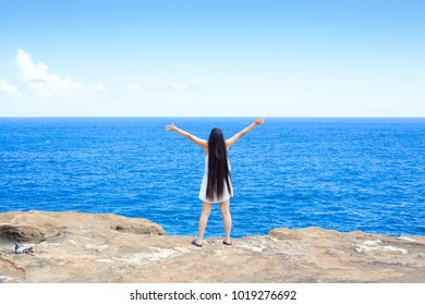 Young biracial Asian Caucasian woman or teen girl standing on cliff overlooking ocean, arms raised to sky back to camera