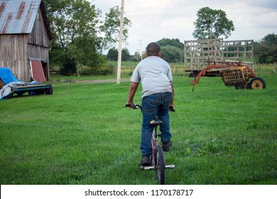 Young, Biracial Boy Riding a Bicycle on a Farm