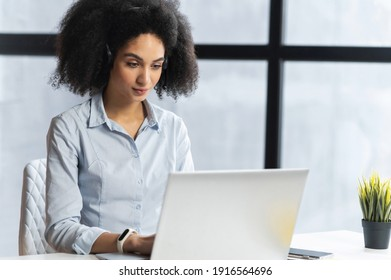 Young biracial woman surfing the internet,typing on the computer,chatting,checking news,making a list of tasks,talking about the news, working from office,making an appointment,at an online meeting