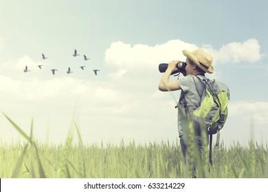 Young birdwatcher looks with his binoculars the bird world