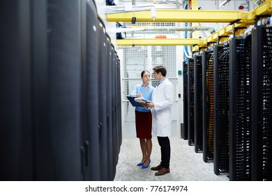 Young bitcoin miners standing by data processing hardware and interacting