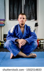 Young bjj brazilian jiu jitsu or judo athlete jujitsu fighter sittin on the tatami mats floor on the training wearing blue kimono gi