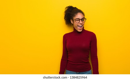 Young black african american girl with blue eyes winking, funny, friendly and carefree gesture
