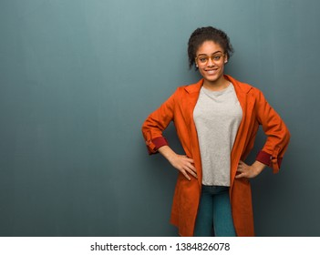 Young black african american girl with blue eyes with hands on hips