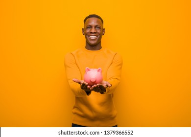 young black african american man holding a piggy bank against orange background