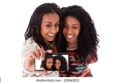 Young black african american teenage girls taking pictures with cell phone, isolated on white background - african people