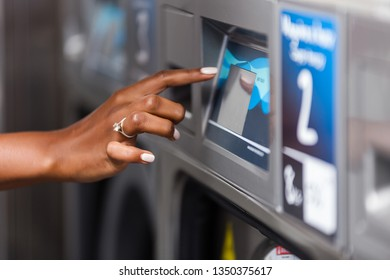 Young black African American woman  hand close up using a washing machine in a laundry