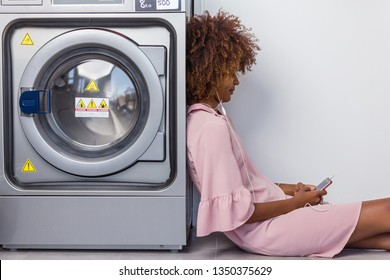 Young black African American woman waiting her clothes to be washed in a automatic laundry