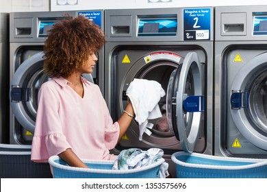 Young black African American woman washing her clothes in a automatic laundry - Translated text : Washing machine super wringing