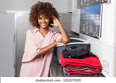 Young black African American woman washing her clothes in a automatic laundry -Transalted text : Dry, empty your pocket,  fill the machine, pay at the central, select the temperature, press start to b