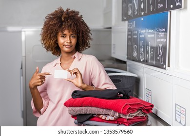 Young black African American woman holding a laundry subscription card - Transalted text : Dry, empty your pocket,  fill the machine, pay at the central, select the temperature, press start to begin