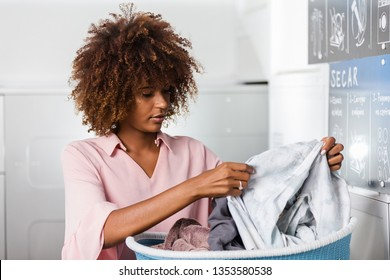 Young black African American woman holding a basket of clothes to be washed in a automatic laundry - Transalted text : Dry, empty your pocket,  fill the machine
