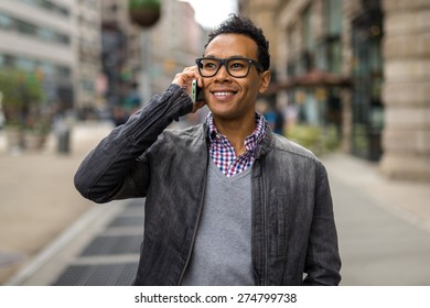Young Black African Asian mixed man in city talking on cell phone