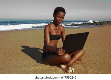 young black African business woman working on laptop at beach