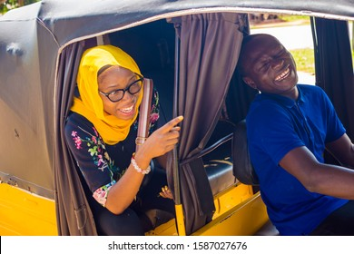young black African female Muslim  woman pointing to her place of destination to a tricycle driver
