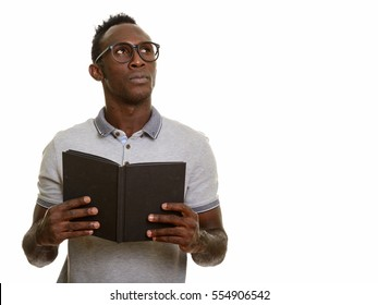 Young black African man holding book while thinking