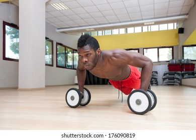 Young black african man portrait doing push up exercise with dumbbells at the gym.