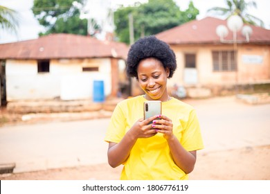 young black African woman with Afro hair standing outside using a modern mobile phone