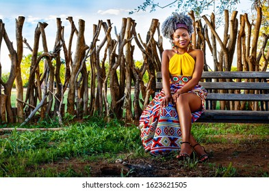 Young black African woman in a traditional African print dress sitting down on a bench