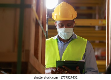 Young black African worker wearing protective face mask working in factory warehouse. Black man checking stock, New normal after covid 19 pandemic crisis. Logistic industry concept.