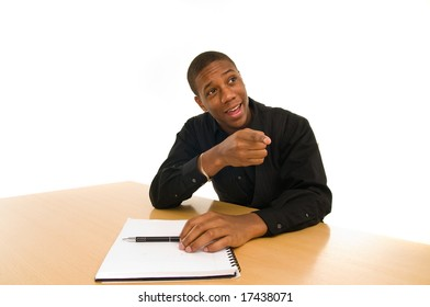 Young black american man sits at table with notebook pointing in exclamation