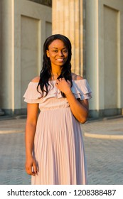 The young black beautiful woman with afro curly dark hair smiling positively at camera. Woman wearing gentle beige dress and standing near big colums in the sunrise.