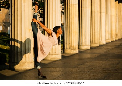 The young black beautiful woman with afro curly dark hair making yoga pose in the cityscape, variation of Natarajasana. Woman wearing gentle beige dress and dancing near big colums in the sunrise.