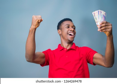 A young black boy  excited celebrating with Nigerian currency