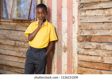 Young black boy with his hand on his face while wearing school clothes