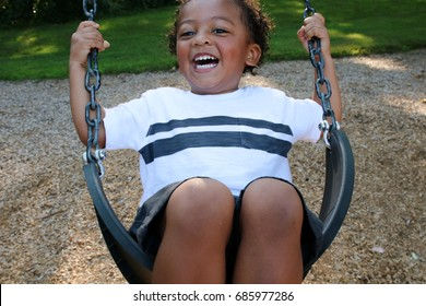 A young black boy is swinging on a swing set in a park. The small child is having fun, smiling on the swing. It is summertime at the playground. He is wearing a t-shirt and shorts and is laughing