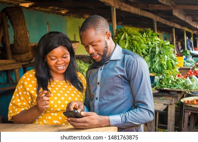 young black business agent meeting with a woman selling in a local market, showing her something on his phone