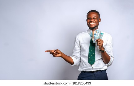 A young Black business man man holding currency notes and pointing to his right,isolated on white studio background-concept on African millennial business and commercial advertisement