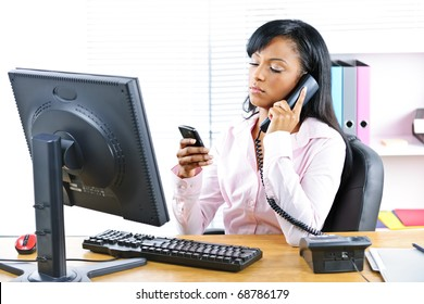 Young black business woman multitasking using two phones in office