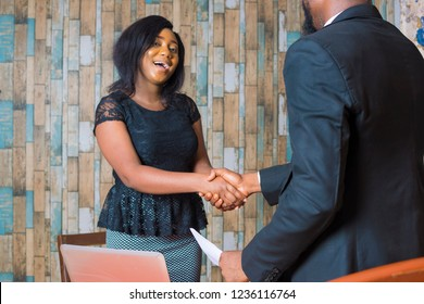 young black business woman shaking a man's hand in her office