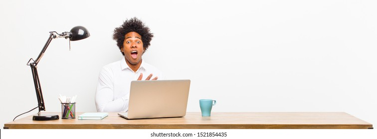 young black businessman feeling shocked, astonished and surprised, with hand on chest and open mouth, saying who, me? on a desk