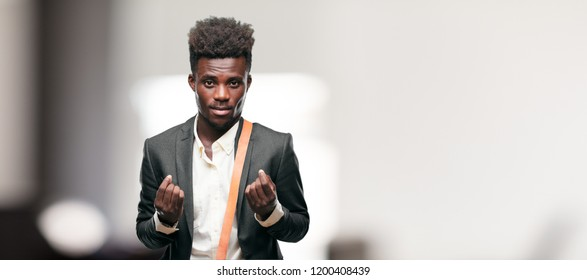 young black businessman looking happy, proud and satisfied, gesturing cash or money, announcing profitable business with a symbol for currency or richness.
