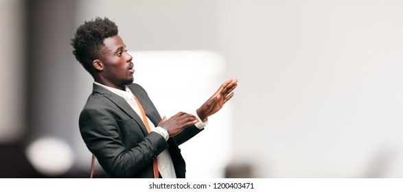young black businessman looking scared, frightened and horrified, screaming in terror, facing doom, feeling very afraid. Lateral or side view.